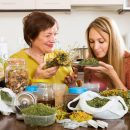 Happy  womans  with medicinal herbs brewing herbal tea