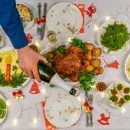 Human hand holding bottle of champagne and pouring sparkling wine into glass against festive served Christmas table. Dinner for New Year party, delicious food. Celebration winter holidays at cozy home