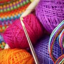 Crochet hook with a ball of colored yarn and knitwear